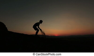 Silhouette of little child playing with sand. Sunset at the mountains on background