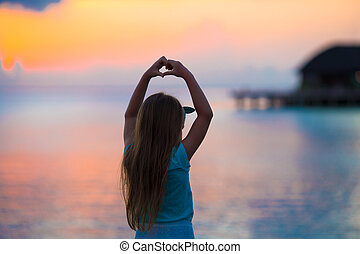 Silhouette of little girl making heart at sunset on the beach