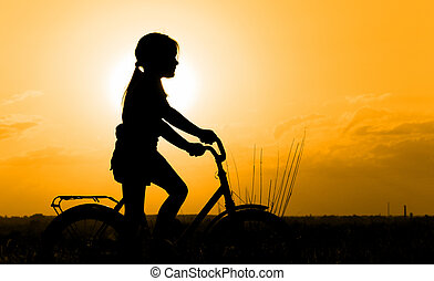 Silhouette of little girl on a bicycle