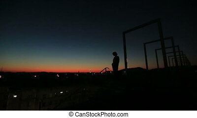 Silhouette of lonely thoughtful woman on the high-tech bridge on red sunset