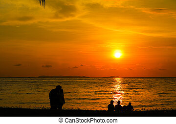 silhouette of lover standing and family sitting look at sunset