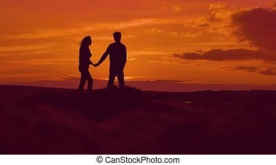 silhouette of lovers holding hands on the beach slow motion video