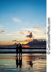 Silhouette of lovers relax on the beach