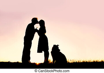 Silhouette of Loving Young Couple Kissing Outside on Date at Sunset
