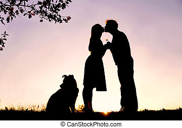 Silhouette of Loving Young Couple Kissing Under Tree at Sunset