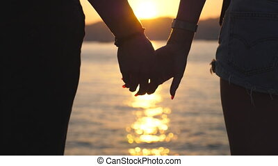 Silhouette of male and female hands holding each other at sunset against an sea background. Young couple joining arms outdoor. Concept of loving and happiness. Close up Rear back view Slow motion