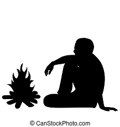 Silhouette of male tourist sitting near fire