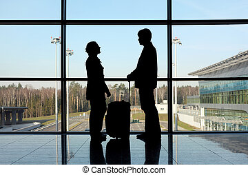 silhouette of man and girl with luggage standing near window in airport side view
