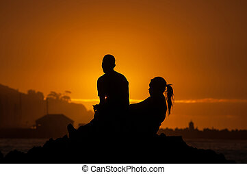 Silhouette of man and women against sunset over a harbor