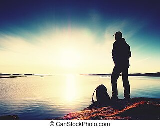 Silhouette of man. Beautiful sunset touch the sea at the horizon, clear blue sky. Hiker enjoy scenery