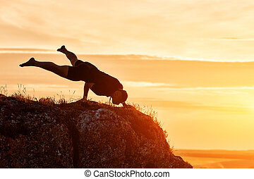 Silhouette of man doing yoga meditation against beautiful sky with clouds.
