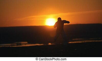 Silhouette of man fighter performing flips on the hill at summer sunset