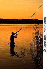 Silhouette of man fishing in water over sunset