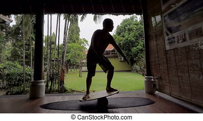 Silhouette of man having training of standing on surfboard...