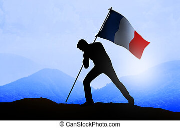 Silhouette of man holding france flag standing on the ...