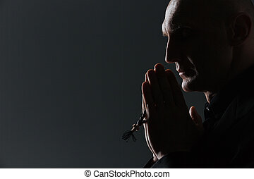 Silhouette of man holding rosary and praying