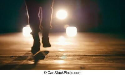 Silhouette of man in garage in front of headlights -feet...