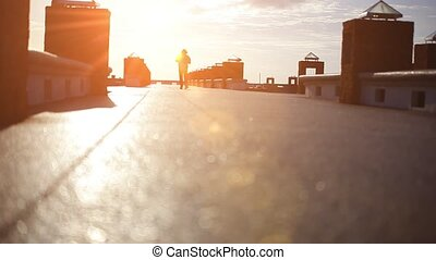 silhouette of man in hat walks over bridge at sunset to the sun. Video