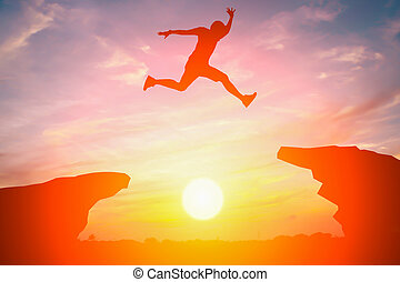 Silhouette of man jump over the cliff obstacle in sunset