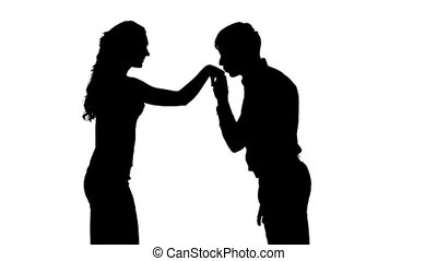 Silhouette of man kissing woman's hand. Slow motion. Close up