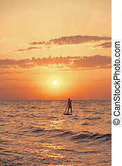 Silhouette of man on a SUP board in sea at sunset.