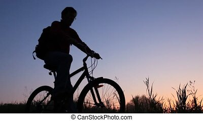 silhouette of man on bicycle stands in field and looks at sky