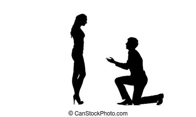 Silhouette of man on one knee and kissing womans hand.