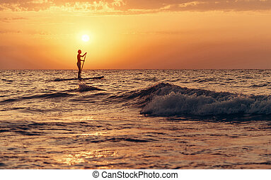Silhouette of man on paddle board in sea at sunset.