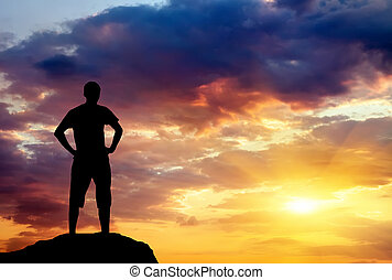 Silhouette of man on rock at sunset. Man on top of mountain. Con