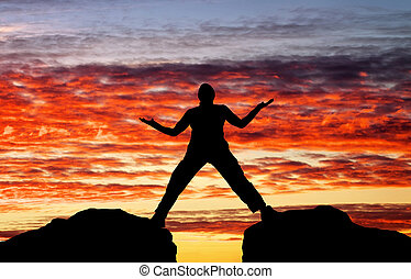 Silhouette of man on sunset fiery sky background