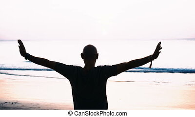 Silhouette of man on the beach over sunset