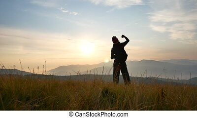 Silhouette of man on the sunset. Freedom concept.