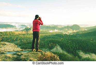 Silhouette of man photographer with camera stand near camp