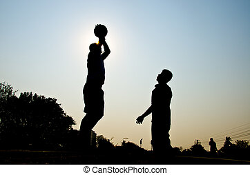 silhouette of man playing basketball