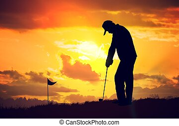 Silhouette of man playing golf at sunset.