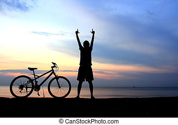 Silhouette of man riding bicycle with beautiful lake near by at sunset