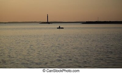 Silhouette of man rows in a boat on water, then turns the...