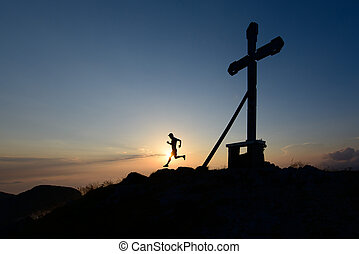 Silhouette of man running in the setting sun on top of a mountain with the cross