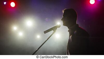 Silhouette of man stand up comedian telling jokes in micropphone on stage.