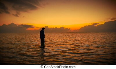 """""""Wide slow push in of solo man stands in stillness of the ocean looking up towards the sky in prayer surrounded by colorful and bright early morning sunrise or sunset. Bowing and raising his head to the sky to a higher power of love, God, and the world."""""""