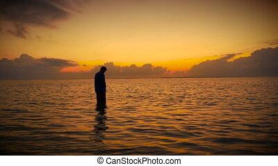 Silhouette of man standing in ocean praying /meditating at...