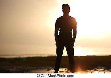 Silhouette of man standing on beach in the sunset at the sea.