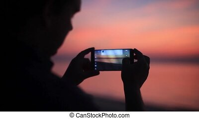 Silhouette of man standing on beach taking photo with smart...