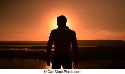 Silhouette of man standing on the top of the hill at sunset and lifting up hands