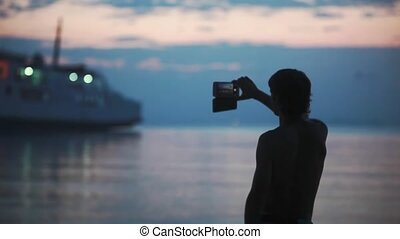 Silhouette of man taking a picture of beautiful evening sky and blurred ship with bokeh lights on the beach on mobile phone.