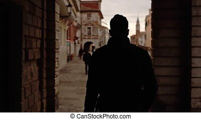 Silhouette of man walking through arch passage along ancient city embankment near narrow channel slow motion backside view