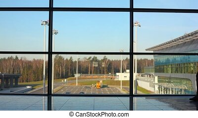 silhouette of man walks against window at airport -...