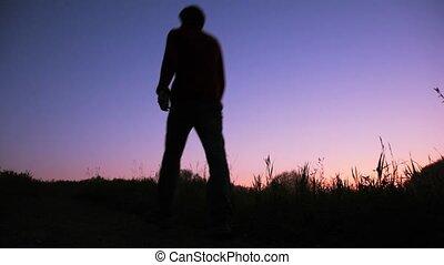 silhouette of man walks uphill against sky