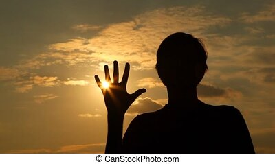 Silhouette of man which palm closes sun