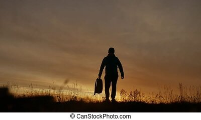silhouette of man with backpack at sunrise in nature field -...